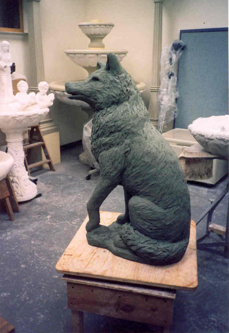 Styrofoam is now covered in clay, showing the Wolf's form.